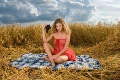Muchacha hermosa en comida campestre en campo de trigo Imagenes de archivo