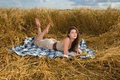 Muchacha hermosa en comida campestre en campo de trigo Fotografía de archivo