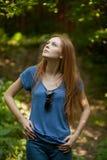 Muchacha hermosa en el azul en el parque que mira para arriba Foto de archivo