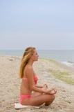 Muchacha hermosa en el bikini que sienta y que mira el mar Fotos de archivo