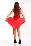 Muchacha hermosa en el bodi rojo que lleva a cabo el corazón de papel Fotos de archivo