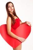 Muchacha hermosa en el bodi rojo que lleva a cabo el corazón de papel Foto de archivo libre de regalías