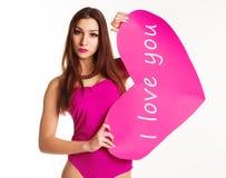 Muchacha hermosa en el bodi rosado que lleva a cabo el corazón de papel Imagenes de archivo