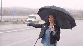 Muchacha hermosa en el camino en fuertes lluvias debajo de un paraguas que intenta coger un coche almacen de metraje de vídeo