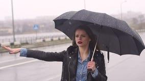 Muchacha hermosa en el camino en fuertes lluvias debajo de un paraguas que intenta coger un coche almacen de video
