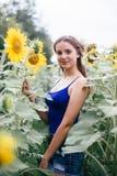 Muchacha hermosa en el campo con los girasoles en pantalones cortos cortos y un chaleco imagen de archivo libre de regalías
