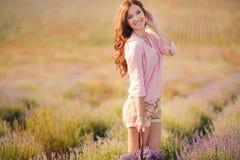 Muchacha hermosa en el campo de la lavanda foto de archivo