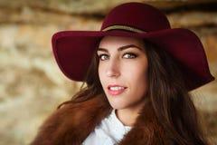 Muchacha hermosa en el cierre marrón del sombrero de fieltro encima del retrato Lanzamiento al aire libre Mire la cámara imagenes de archivo