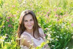 Muchacha hermosa en el claro con las flores del prado Foto de archivo
