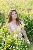 Muchacha hermosa en el claro con las flores del prado Foto de archivo libre de regalías