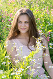 Muchacha hermosa en el claro con las flores del prado Fotos de archivo libres de regalías