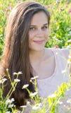 Muchacha hermosa en el claro con las flores del prado Imagenes de archivo