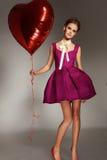Muchacha hermosa en el día de tarjeta del día de San Valentín rojo del corazón del baloon del vestido de noche Foto de archivo