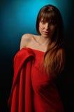 Muchacha hermosa en el estudio que lleva una capa roja Imagen de archivo libre de regalías