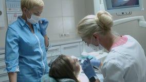 Muchacha hermosa en el examen del dentista del doctor metrajes