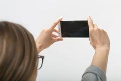 Muchacha hermosa en el fondo blanco con el teléfono Fotografía de archivo libre de regalías