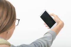 Muchacha hermosa en el fondo blanco con el teléfono Imagen de archivo libre de regalías