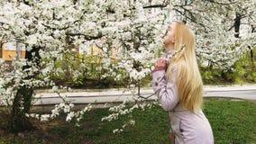 Muchacha hermosa en el fondo de los árboles de la flor almacen de metraje de vídeo