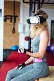 Muchacha hermosa en el gimnasio con las auriculares de VR Fotografía de archivo libre de regalías