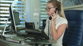 Muchacha hermosa en el mostrador de recepción que contesta a la llamada en centro médico metrajes