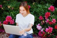 Muchacha hermosa en el ordenador portátil del parkwith Fotografía de archivo libre de regalías