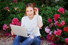 Muchacha hermosa en el ordenador portátil del parkwith Imagen de archivo