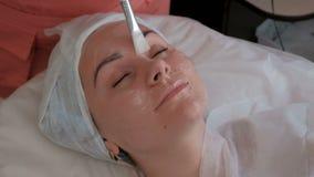 Muchacha hermosa en el procedimiento cosmetological Un cosmetólogo en guantes azules pone un gel transparente con un cepillo blan almacen de video