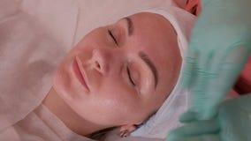 Muchacha hermosa en el salón de belleza El cosmetólogo en guantes azules pone un gel transparente en la cara de una mujer joven E almacen de metraje de vídeo