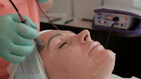 Muchacha hermosa en el salón de belleza Masaje facial de Microcurrent Procedimiento de Cosmetological usando la corriente galváni almacen de video