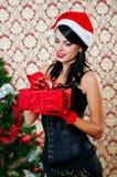 Muchacha hermosa en el sombrero de santa cerca de un árbol de navidad Imagenes de archivo