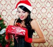 Muchacha hermosa en el sombrero de santa cerca de un árbol de navidad Fotografía de archivo