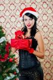 Muchacha hermosa en el sombrero de santa cerca de un árbol de navidad Imágenes de archivo libres de regalías