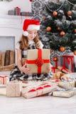 Muchacha hermosa en el sombrero de santa que desempaqueta regalos de Navidad Fotografía de archivo