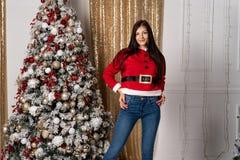 Muchacha hermosa en el suéter de santa después de adornar la presentación del árbol de navidad, mirando la cámara imagen de archivo