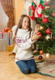 Muchacha hermosa en el suéter que se sienta en piso en la sala de estar y el de Fotografía de archivo libre de regalías