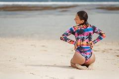 Muchacha hermosa en el traje de baño que se sienta en la playa y el lookin blancos de la arena adelante foto de archivo