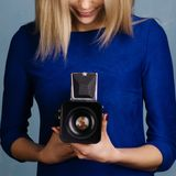 Muchacha hermosa en el vestido azul que mira en cámara media vieja del formato foto de archivo