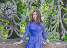 Muchacha hermosa en el vestido azul que presenta en la cerca del labrado-hierro Fotos de archivo libres de regalías