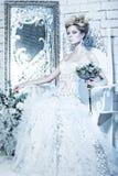 Muchacha hermosa en el vestido blanco en la imagen de la reina de la nieve con una corona en su cabeza Foto de archivo libre de regalías