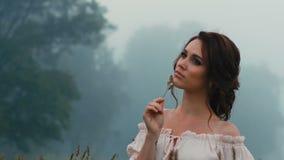Muchacha hermosa en el vestido blanco que presenta en c?mara almacen de metraje de vídeo