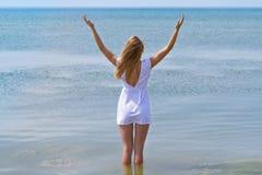 Muchacha hermosa en el vestido blanco que se coloca en el agua, haciendo frente al amanecer Fotos de archivo