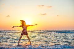 Muchacha hermosa en el vestido colorido que salta como una estrella en agua del océano en puesta del sol imagen de archivo