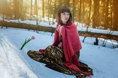 Muchacha hermosa en el vestido de oro que se sienta en la nieve en el bosque del sol de la primavera y el tulipán de los tactos fotografía de archivo libre de regalías