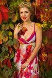 Muchacha hermosa en el vestido del color que presenta en un fondo de hojas Fotos de archivo libres de regalías