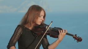 Muchacha hermosa en el vestido del tracery que toca el violín almacen de metraje de vídeo