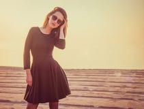 Muchacha hermosa en el vestido negro que se coloca en la playa Fotos de archivo