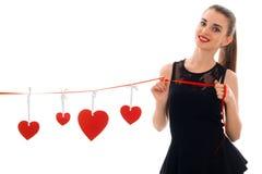 Muchacha hermosa en el vestido negro que sostiene una cinta con los corazones y la sonrisa rojos Fotografía de archivo