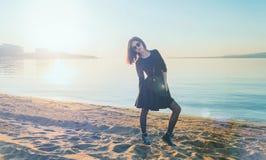Muchacha hermosa en el vestido que se coloca en la playa Imagen de archivo