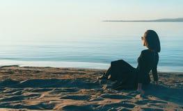 Muchacha hermosa en el vestido que se sienta en la playa Imagenes de archivo