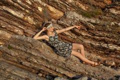 Muchacha hermosa en el vestido que se sienta en un fondo del acantilado en la puesta del sol Foto de archivo libre de regalías